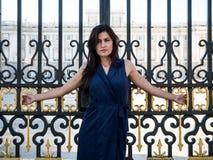Mooie donkerbruine die vrouw op de poort van een paleis wordt gekruisigd Royalty-vrije Stock Afbeelding
