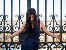 Mooie donkerbruine die vrouw op de poort van een paleis wordt gekruisigd Royalty-vrije Stock Foto's