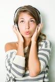 Mooie donkerbruine iwearing hoofdtelefoons, het fluiten. Stock Foto's