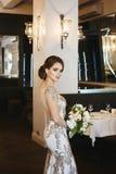 Mooie donkerbruine jonge modelvrouw met huwelijkskapsel en blauwe ogen in lange modieuze avondjurk die houden stock afbeeldingen