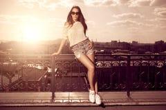 Mooie donkerbruine jonge vrouw die zonnebril, witte borrels dragen, Stock Foto