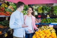 Mooie donkerbruine meisje en vriend het kopen citrusvruchten Royalty-vrije Stock Foto's