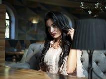 Mooie donkerbruine meisjeszitting bij een lijst in een restaurant en het bekijken de camera stock afbeelding