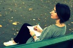 Mooie donkerbruine meisjeszitting op de bank en het schrijven in een agenda Royalty-vrije Stock Afbeelding