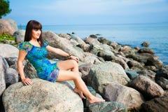 Mooie donkerbruine meisjeszitting op strandstenen Stock Foto's