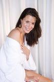 Mooie donkerbruine vrouw die badjas draagt stock afbeelding