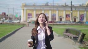 Mooie donkerbruine vrouw die de stadsstraat lopen en op de celtelefoon spreken Vrouw die met koffie lopen om te gaan stock video