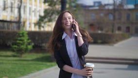 Mooie donkerbruine vrouw die de stadsstraat lopen en op de celtelefoon spreken Vrouw die met koffie lopen om te gaan stock footage