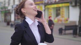 Mooie donkerbruine vrouw die de stadsstraat lopen en op de celtelefoon spreken Vrouw die met koffie lopen om te gaan