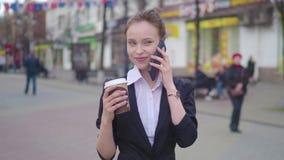 Mooie donkerbruine vrouw die de stadsstraat lopen en op de celtelefoon spreken Vrouw die met koffie lopen om te gaan stock videobeelden