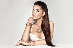 Mooie donkerbruine vrouw die heel wat juwelen dragen. Stock Afbeelding