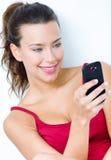 Mooie donkerbruine vrouw die mobiel kijken royalty-vrije stock foto's