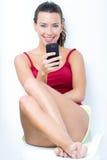Mooie donkerbruine vrouw die mobiel kijken stock afbeeldingen