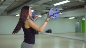 Mooie donkerbruine vrouw die oefeningen met een barbell doen Het concept van de geschiktheid stock video