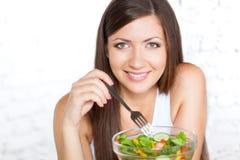 Mooie donkerbruine vrouw die salade eet Royalty-vrije Stock Afbeelding