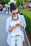 Mooie donkerbruine vrouw die slimme telefoon in de stad met behulp van Royalty-vrije Stock Afbeeldingen