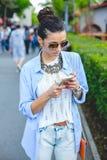 Mooie donkerbruine vrouw die slimme telefoon in de stad met behulp van Royalty-vrije Stock Fotografie