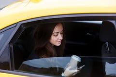 Mooie donkerbruine vrouw die telefoon in taxi kijken Royalty-vrije Stock Fotografie
