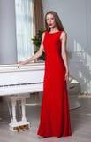 Mooie donkerbruine vrouw in een rode kleding Het schot van de studio Lang haar Rode Lippen Royalty-vrije Stock Fotografie