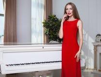 Mooie donkerbruine vrouw in een rode kleding Het schot van de studio Lang haar Rode Lippen Stock Fotografie