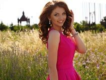 Mooie donkerbruine vrouw in het elegante kleding stellen op lavendelgebied Royalty-vrije Stock Foto's