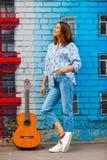 Mooie donkerbruine vrouw in jeans met een gitaar royalty-vrije stock fotografie