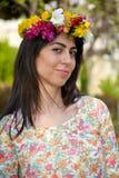 Mooie donkerbruine vrouw met bloemkroon in de de lentetuin Royalty-vrije Stock Afbeelding