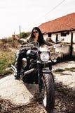 Mooie donkerbruine vrouw met een klassieke motorfiets c royalty-vrije stock afbeelding
