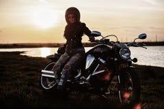 Mooie donkerbruine vrouw met een klassieke motorfiets c stock fotografie