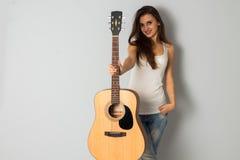 Mooie donkerbruine vrouw met gitaar Stock Afbeelding