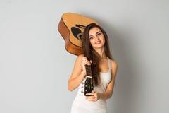 Mooie donkerbruine vrouw met gitaar in handen Royalty-vrije Stock Foto