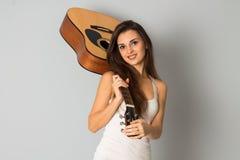 Mooie donkerbruine vrouw met gitaar in handen Stock Foto's