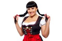 Mooie donkerbruine vrouw met vlechten in het Beierse geklede glimlachen Stock Afbeelding