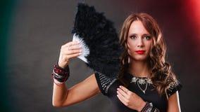 Mooie donkerbruine vrouw met zwarte in hand ventilator Stock Afbeeldingen
