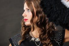 Mooie donkerbruine vrouw met zwarte in hand ventilator Royalty-vrije Stock Foto's