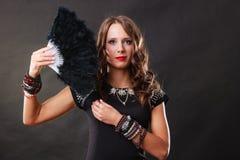 Mooie donkerbruine vrouw met zwarte in hand ventilator Stock Fotografie