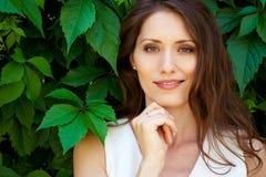 Mooie donkerbruine vrouw in openlucht met groen milieu Royalty-vrije Stock Afbeeldingen