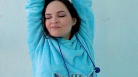 mooie donkerbruine vrouw in pluizige blauwe pyjama'sgeeuwen en rek vroeg in de ochtend in de slaapkamer stock video