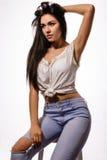 Mooie donkerbruine vrouw in witte bovenkant en jeans op stoel Stock Foto's
