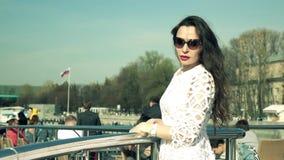 Mooie donkerbruine vrouw in witte kleding die zich op het dek van een boot bevinden stock videobeelden