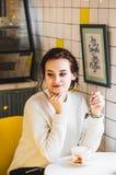 Mooie donkerbruine vrouw in witte sweater in een koffie het drinken koffie Hipster wit en geel binnenland van koffie royalty-vrije stock foto's