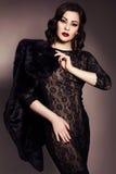 Mooie donkerbruine vrouw in zwarte kleding en bontjas met evenin Royalty-vrije Stock Afbeeldingen