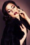 Mooie donkerbruine vrouw in zwarte kleding en bontjas met evenin Royalty-vrije Stock Afbeelding