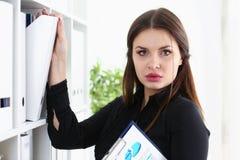 Mooie donkerbruine vrouwelijke bediende die naar juist document zoeken Stock Afbeeldingen