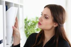 Mooie donkerbruine vrouwelijke bediende die naar juist document zoeken Stock Fotografie