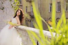 Mooie donkerbruine vrouwenbruid in een tuinpark in wit huwelijk Stock Foto's