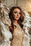 Mooie donkerbruine vrouwentribunes met gouden en witte vleugels in Stock Foto's