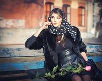 Mooie donkerbruine vrouwenzitting buiten Royalty-vrije Stock Foto's