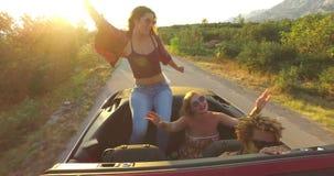 Mooie donkerbruine zitting op kap van het convertibele berijden met haar vrienden stock footage