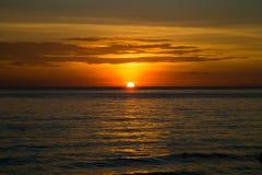 Mooie dramatische gouden hemel over het overzees en bezinning in zonsondergangtijd in de zomer stock foto's